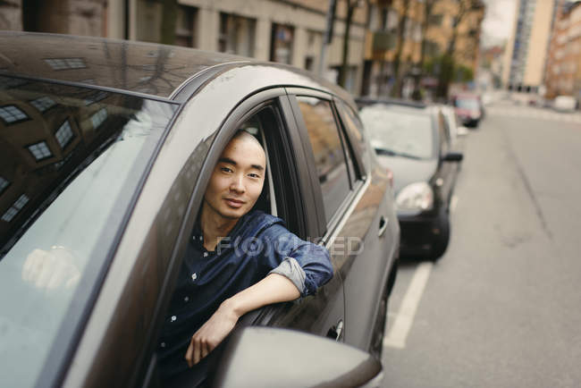 Young man in car, differential focus — Stock Photo