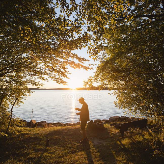 Mittlerer erwachsener Mann, der bei Sonnenuntergang mit Angelrute am Fluss steht — Stockfoto