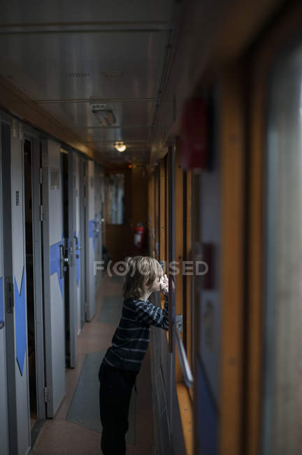 Boy looking through train window, selective focus — Foto stock