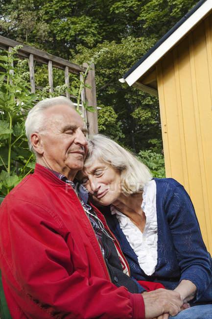 Старшая пара, сидящая вместе, сосредоточьтесь на переднем плане — стоковое фото