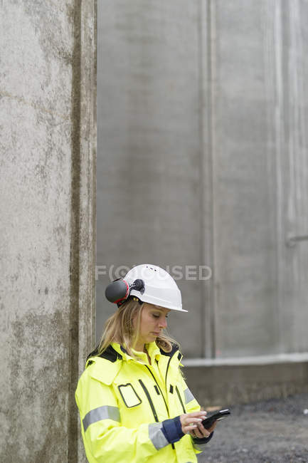 Engineer in protective workwear working at construction site — Stock Photo