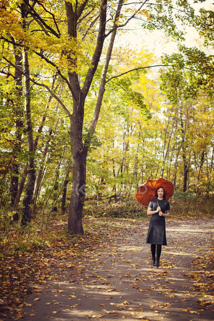 Woman with red umbrella walking in park at autumn — Stock Photo