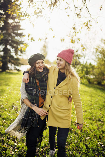 Two young women embracing each other, focus on foreground — Stock Photo