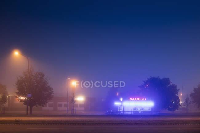 Illuminated kiosk by road at night, northern europe — Stock Photo