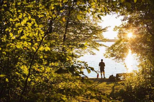 Силуэт человека, стоящего с веслом на закате — стоковое фото