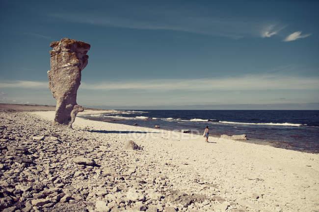 Vista panorámica de la playa de arena y la mujer de pie sobre el fondo - foto de stock