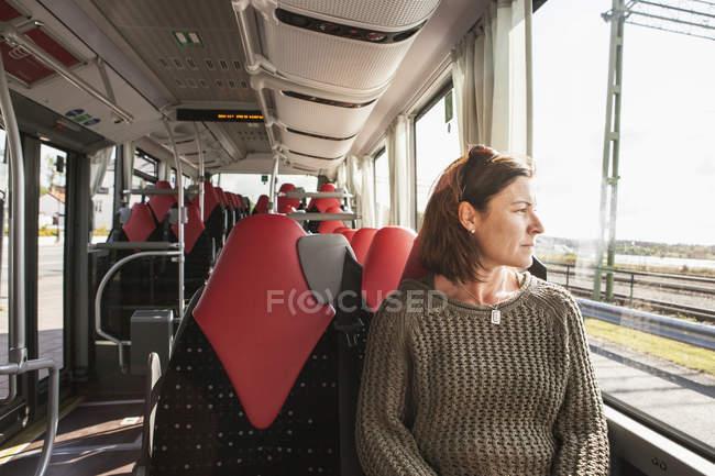 Woman sitting on train and looking in window — Fotografia de Stock