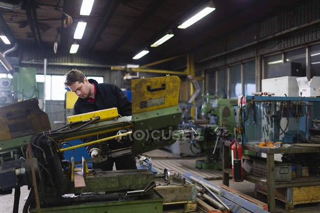 Young man working in workshop, focus on foreground — Stock Photo