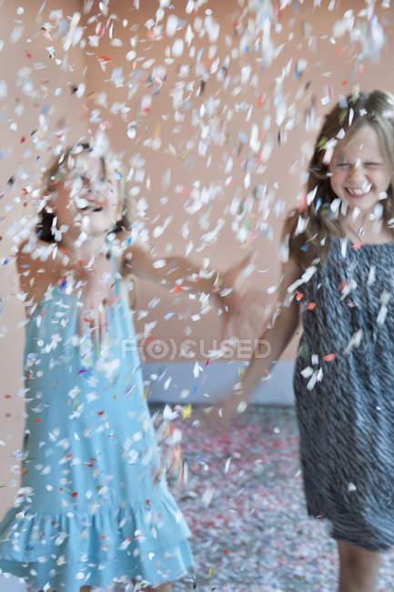 Два молодих дівчат граючи в конфетті, вибіркове фокус — стокове фото