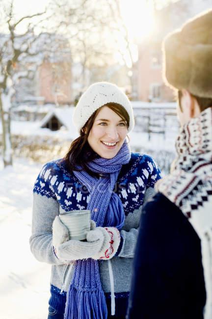 Молода жінка носить в'язати шапка або рукавиці проведення гарячий шоколад — стокове фото