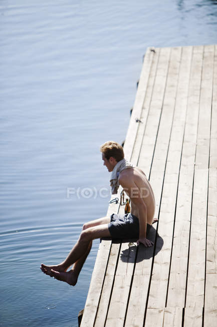 Молода людина, що сидить на дерев'яні jetty озера — стокове фото