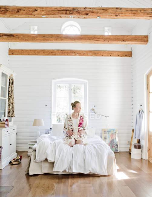 Mulher grávida meio-adulta sentada na cama e olhando para longe — Fotografia de Stock