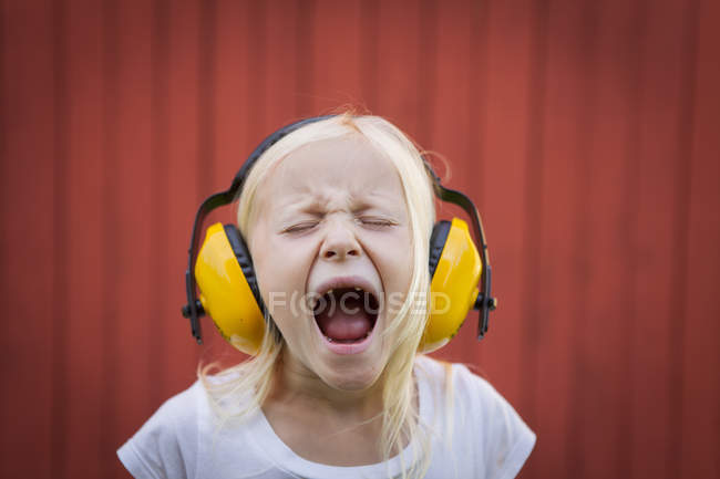Portrait of blonde girl wearing ear muffs, screaming with eyes closed — Stock Photo