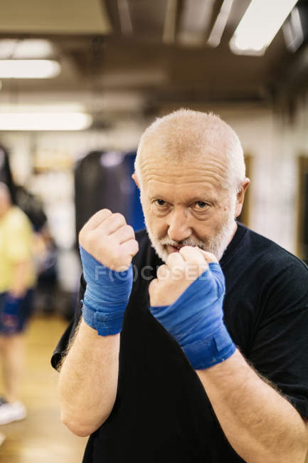 Senior man with fists raised at boxing training, focus on foreground — Stock Photo