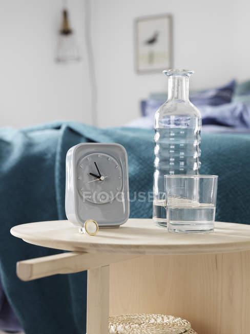 Reloj despertador y botella en el dormitorio, enfoque selectivo - foto de stock