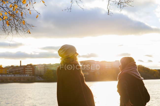 Two women by river at sunset, selective focus — Stockfoto