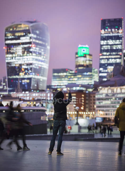 Молода людина фотографує місто Лондон уночі — стокове фото