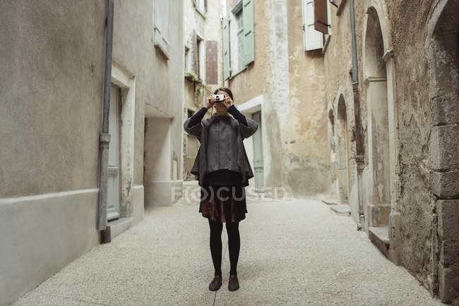 Young woman photographing in old town — Stock Photo