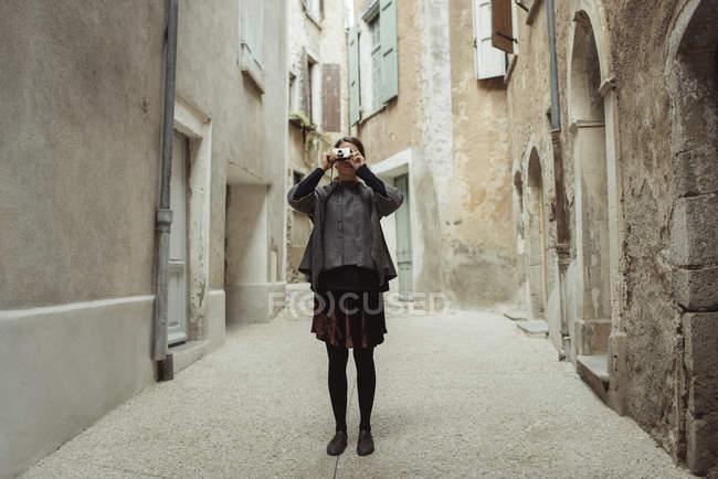 Jeune femme photographiant dans la vieille ville — Photo de stock