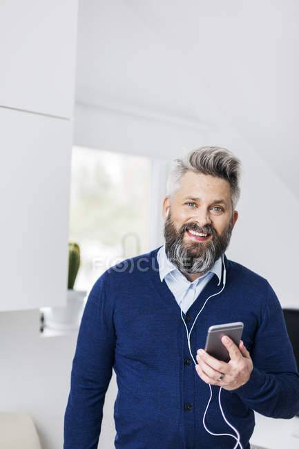 Man with earphones listening on cell phone — Stock Photo