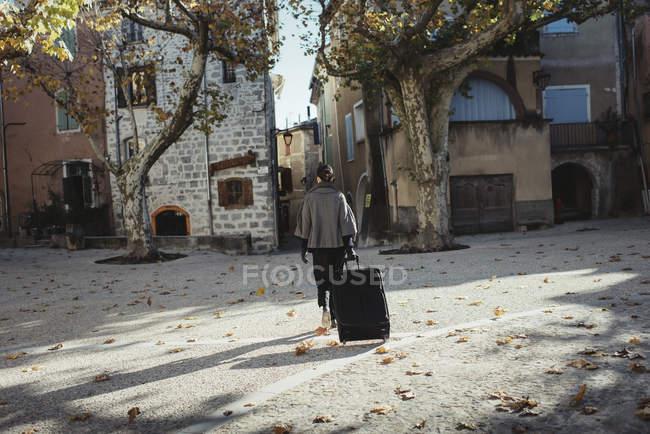 Vista posteriore di giovane donna che cammina con i bagagli in tutta Piazza della città — Foto stock