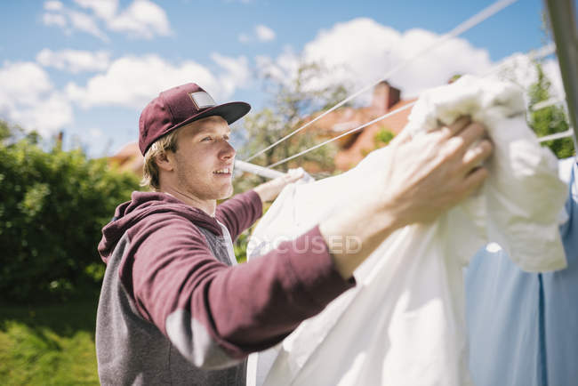 Young man hanging laundry, differential focus — Stock Photo