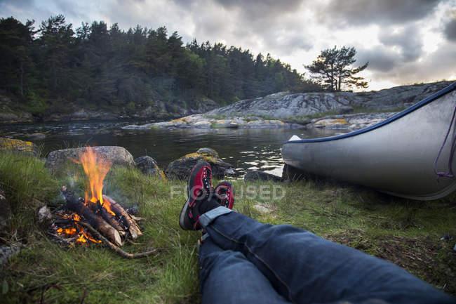 Persönliche Perspektive des am Lagerfeuer am Flussufer liegenden Mannes — Stockfoto