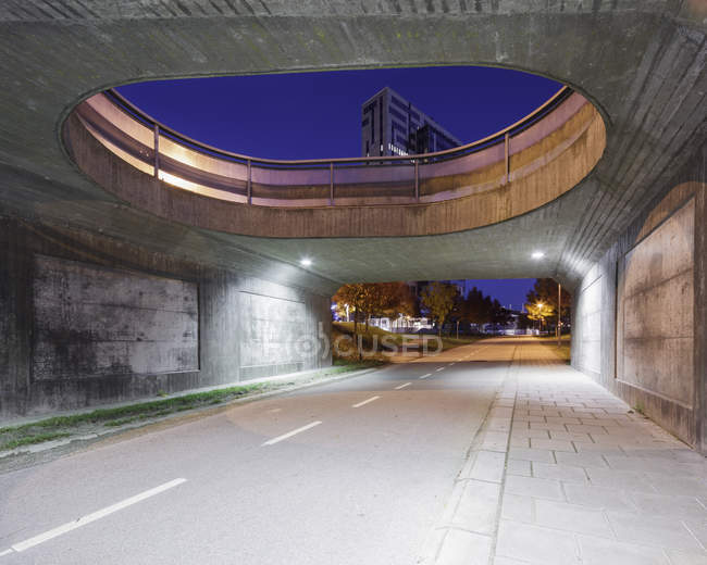 Road under bridge with buildings in background — Stock Photo