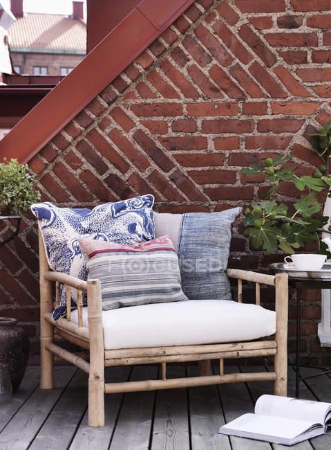 Кресло с подушками к кирпичной стене — стоковое фото
