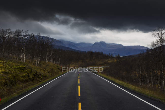 Rural road under storm clouds in Sweden — Stock Photo