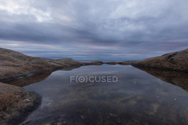 Rock pool under overcast sky in north of Sweden — Stock Photo