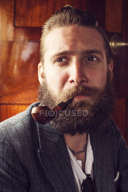 Portrait of bearded man smoking pipe, selective focus — Stock Photo