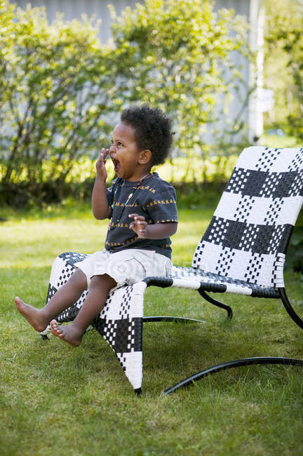 Boy sitting in lounge chair, selective focus — Foto stock