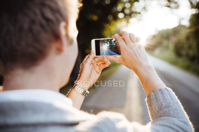 Man photographing road at sunset, selective focus — Stock Photo