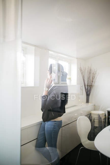 Woman talking on smart phone behind window — Stock Photo