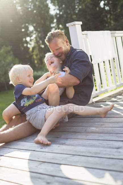 Father playing with sons outdoors, selective focus — Stock Photo