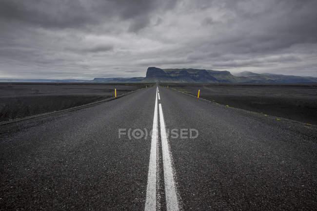 Route asphaltée contre les nuages d'orage — Photo de stock