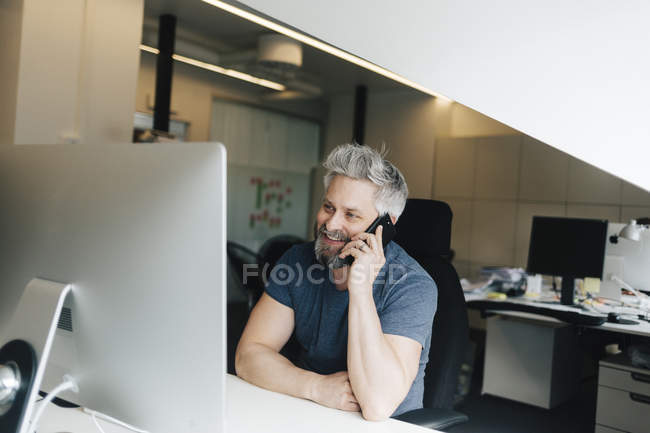 Man talking on smartphone at office desk, focus on foreground — Stock Photo