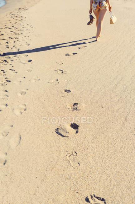 След в песке на пляже, женщина в фоновом режиме — стоковое фото