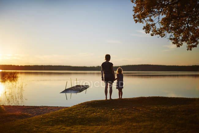 Rückansicht von Mutter und Tochter am See bei Sonnenuntergang — Stockfoto