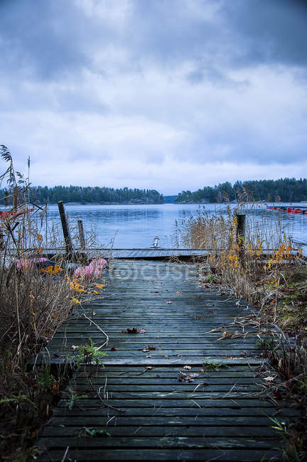 Wooden pier and lake, diminishing perspective — Stock Photo