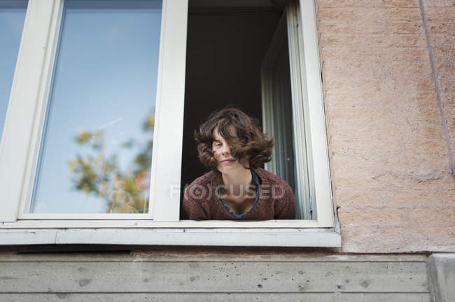 Low angle view of young woman leaning in window — Fotografia de Stock