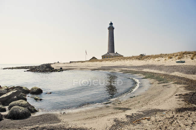 Lighthouse on beach against clear sky, northern europe — Stock Photo