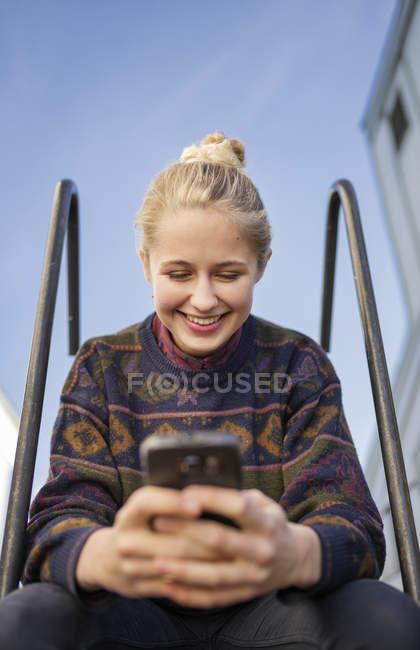 Jovem mulher usando telefone, foco diferencial — Fotografia de Stock