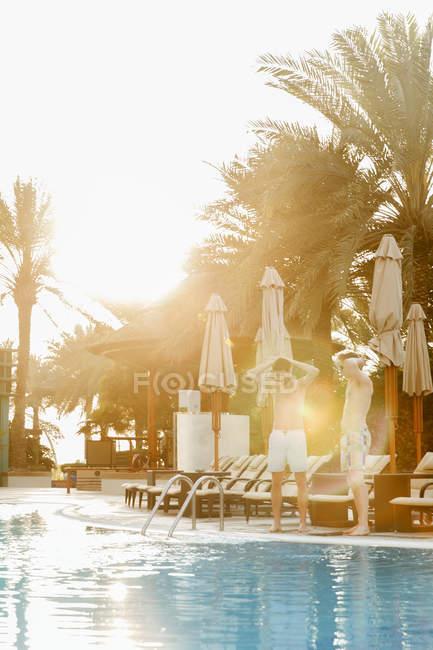 Men standing by swimming pool at summer — Foto stock