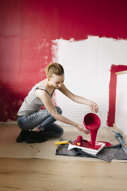 Woman pouring paint into paint tray — Stock Photo