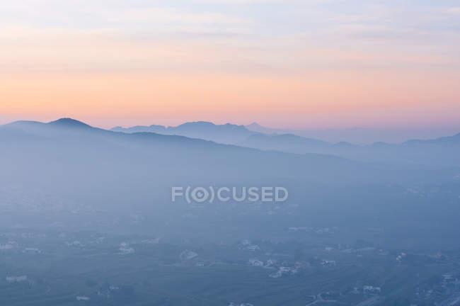 Краєвид з пагорбами, в туман на світанку — стокове фото