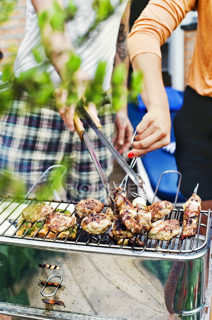 Couple grilling meat on barbecue, differential focus — Stock Photo