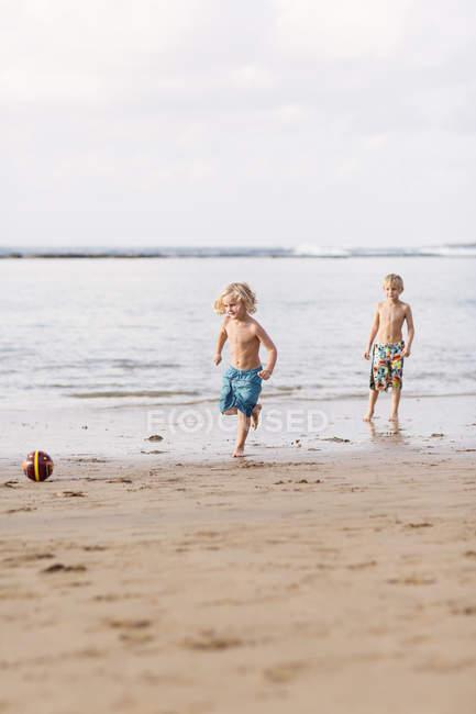 Мальчики играют с мячом на пляже, избирательный фокус — стоковое фото