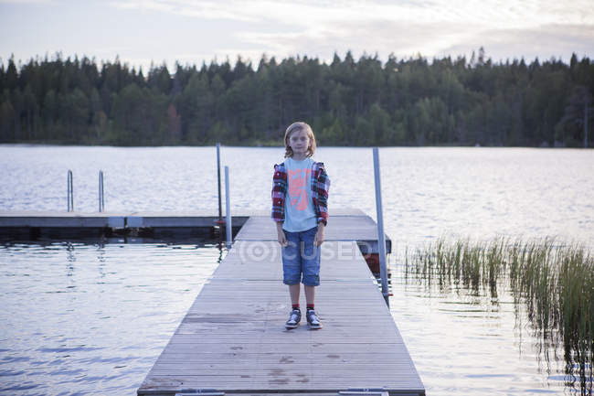 Portrait of boy standing at pier extending into lake — Stock Photo